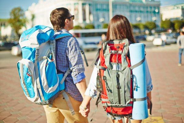 casal viajando com mochilas nas costas