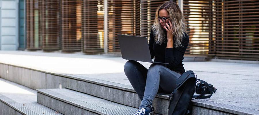 imagem de uma mulher sentada em uma escada pública com um notebook no colo e uma mochila ao lado