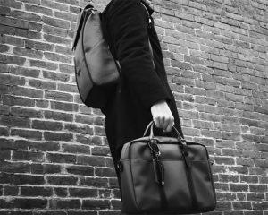 imagem de um homem carregando uma mochila e uma pasta executiva